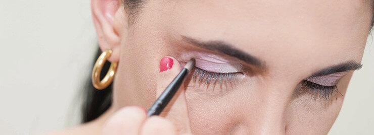 Close de um rosto feminino, com destaque para os olhos, que estão delineados com traços finos. Na pálpebra direita, pincel faz esfumeado com sombra lilás.