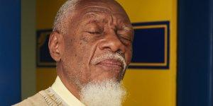Close de um senhor, pele morena, cabelos e barba brancos. Ao fundo, porta amarela, com identificação em azul