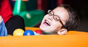 Close de um menino de aproximadamente 8 anos, cabelos curtos, óculos e largo sorriso. Está na piscina de bolinhas e à sua frente 3 bolas nas cores amarelo, azul e vermelho