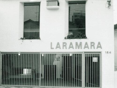 Fachada da primeira sede de Laramara. Um sobrado com grades brancas; duas grandes janelas retangulares, cujos vidros refletem parte do entorno. Acima da grade, lê-se Laramara e à direita, o número 164