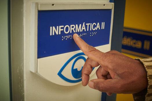 Placa de identificação acessível, com tipos brancos em fundo azul, onde se lê Informática II em tipos ampliados e em Braille. Abaixo, logo da Laramara