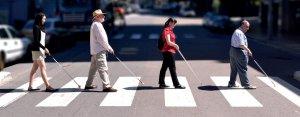4 adultos, sendo, alternadamente, um homem e uma mulher, atravessam uma rua sob a faixa de pedestres, com suas bengalas longas