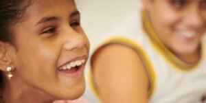 Em primeiro plano, close de uma menina de aproximadamente 10 anos, com largo sorriso e, ao fundo, um menino da mesma idade, também sorri