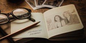Em primeiro plano, um livro aberto. Na página da esquerda, lê-se História da Laramara e sobre ela, um par de óculos e um lápis. Na página da direita, uma fotografia em preto e branco, com Sr. Victor Siaulys à esquerda, Lara ao centro e Sra. Mara Siaulys à direita. Ao fundo, visão parcial de fotografias em papel