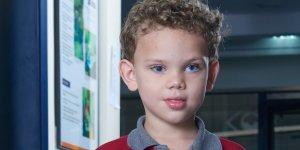 Em primeiro plano, close de um menino de aproximadamente 7 anos de idade, cabelos loiros e cacheados, olhos claros