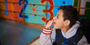 Perfil de um menino de aproximadamente 6 anos, cabelos curtos e escuros. Usa um moletom cinza de mangas compridas e está sentado em sua cadeira adaptada. Ao fundo, prateleira coloridas, numeradas de 1 a 3