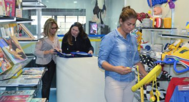 Em primeiro plano, uma jovem, estatura mediana e cabelos presos, explora brinquedo adaptado. Ao fundo, duas jovens, com o Livro Sensorial. Ao redor, brinquedos e livros