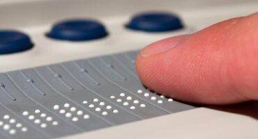 Linha Braille, com destaque para a ponta de um dedo indicador sobre ela