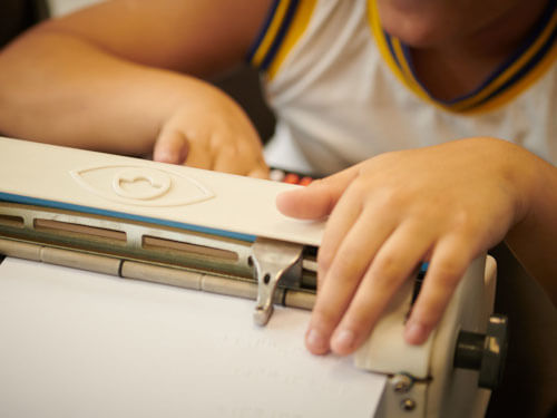 Detalhe de uma máquina braile, com as mãos de um menino, sendo que a mão direita toca uma das teclas, enquanto a esquerda, faz a leitura no papel