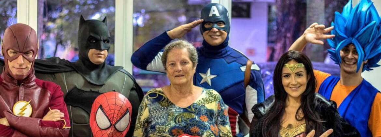 Grupo Heróis do bem. Em primeiro plano, uma senhora de cabelos grisalhos e curtos. À sua esquerda, close da máscara do Homem Aranha e ao lado, o Flash. Á sua direita, Mulher Maravilha e atrás dela, Batman, Capitão América e Goku, que fazem gesto de continência