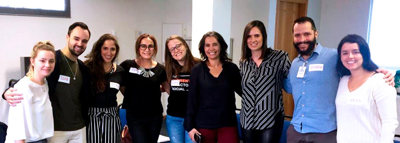 Foto com cinco colaboradores da Jonhson & Johnson, uma voluntária da Phomenta e três funcionários da Laramara. Na imagem, eles estão todos abraçados.