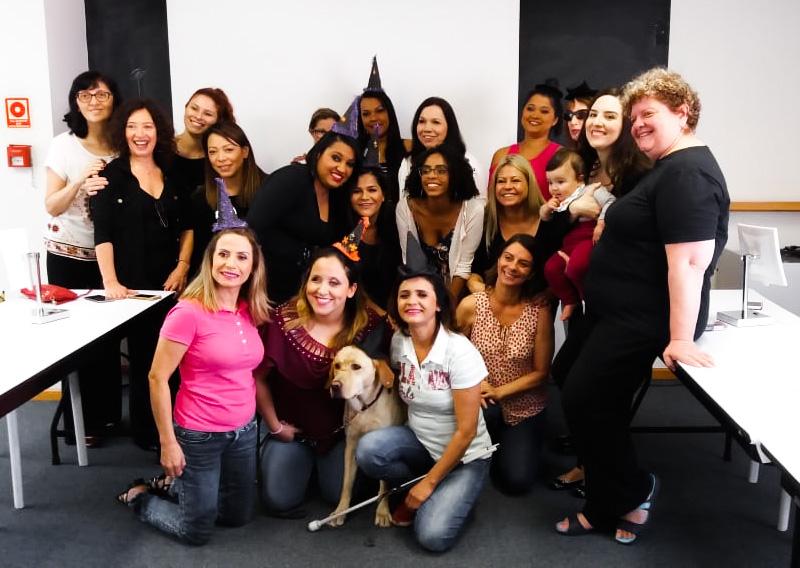 Imagem das alunas, maquiadoras e profissionais da Laramara, que participaram da sexta edição do Curso de Automaquiagem. Todas sorriem e posam para a foto. As alunas estão usando aderaços referente ao Halloween.