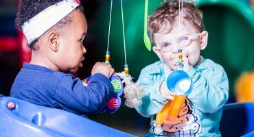 Dois bebês, brincando com um móbile, cujo os objetos pendurados nele são, uma colher verde, um chocalho roxo, uma boneca pequena e uma caneca azul.