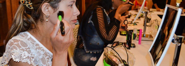 Foto da aula do curso de automaquiagem. Na imagem, duas alunas com baixa visão, estão com um pincel de blush, aplicando a maquiagem nas maçãs do rosto.