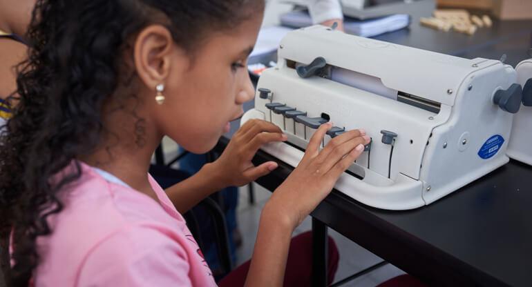 Menina escrevendo um texto na máquina braille