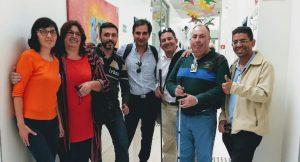 Foto dos visitantes e colaboradores da Laramara. Eles estão posando em pé no corredor das salas do Proceja.