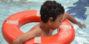 criança na piscina apoiada em uma bóia
