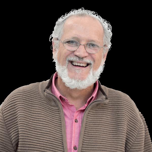 Foto em plano americano, jovem senhor, cabelos curtos e grisalhos, barba e bigode grisalhos. Usa óculos e tem largo sorriso no rosto. Usa um casaco de gola alta listrado em tons pastéis por cima de uma camisa cor de rosa.