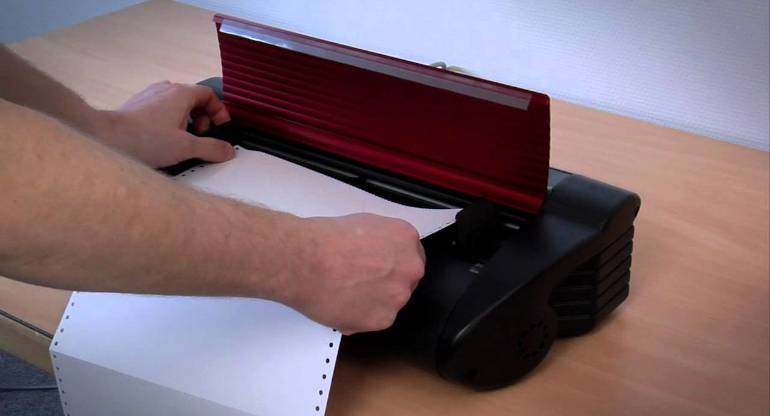 Mãos colocando papel contínuo em uma das impressoras braille abordadas no manaul