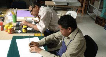 Ateliê da Laramara com dois alunos sentados lado a lado realizando atividades de desenho e pintura. Em primeiro plano, temos um aluno cego usando a técnica da prancha telada. Em segundo plano, vemos um aluno com baixa visão realizando a técnica de pintura com guache sobre papel