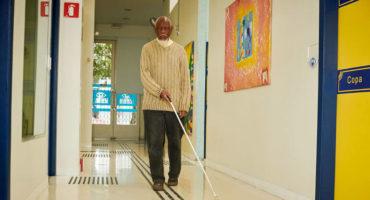 Homem de meia idade, negro, de cabelos, barba e bigode brancos. Está de calça jeans e blusa de lá bege de mangas compridas. Caminha por um corredor com piso tátil e na mão direita, bengala longa.