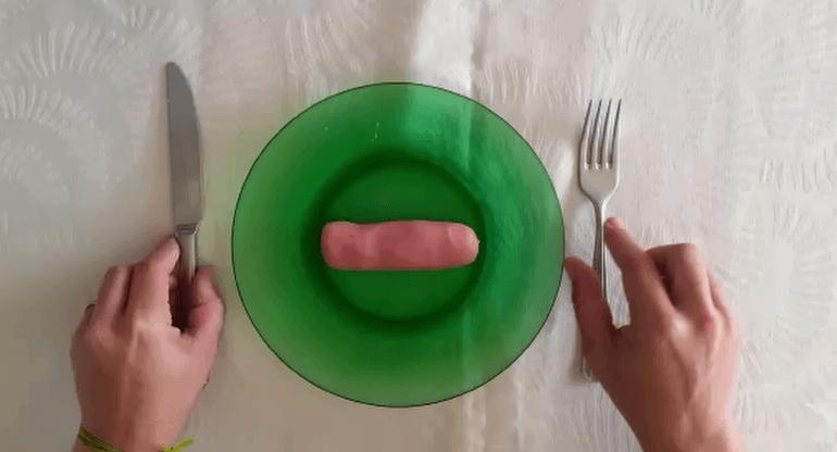 Prato na cor verde no centro da imagem. No prato há uma massinha de modelar representando uma salsicha. À esquerda mão segurando uma faca e à direita mão segurando um garfo