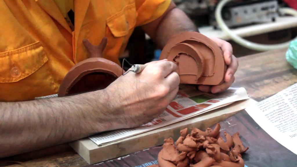 Close nas mãos de Ricardo Barbosa, Arte Educador do Programa de Jovens e Adultos (Proceja), da Laramara. Na mão esquerda, segura uma peça de argila e na mão direita, um pincel com cola líquida, que está sobre a peça.