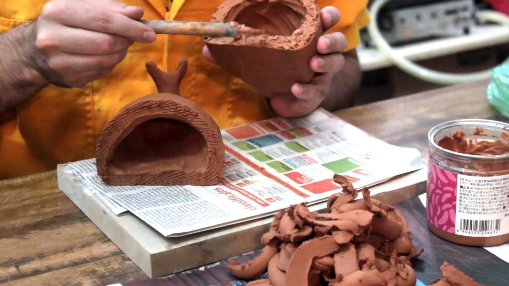 Close nas mãos de Ricardo Barbosa, Arte Educador do Programa de Jovens e Adultos (Proceja), da Laramara. Na mão esquerda, segura uma peça de argila e na mão direita, um pincel de corte, que está sobre a peça.
