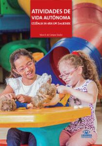 Duas meninas de aproximadamente 7 anos, cabelos longos e óculos, estão sentadas lado a lado, em frente à uma mesinha amarela. Em cima da mesa, os bonecos Tato e Tati. Ao fundo, parte do escorregador colorido do Laraparque.